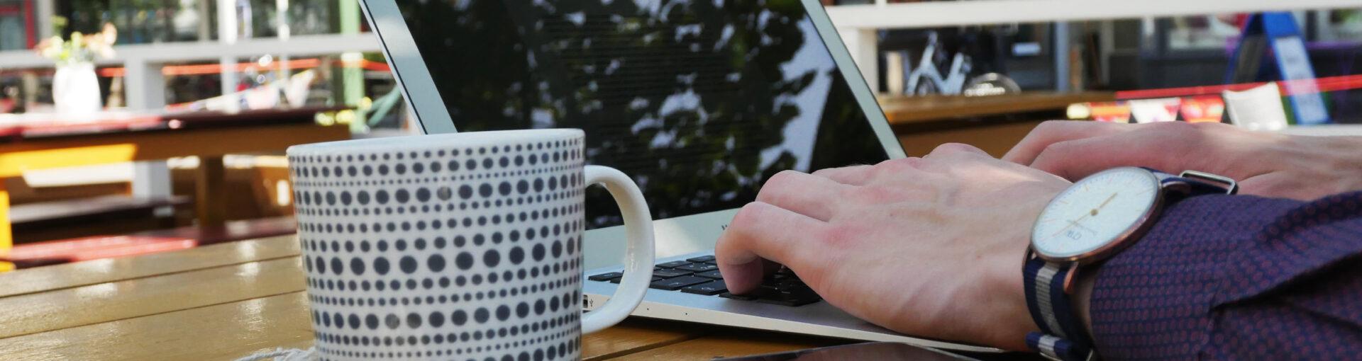 Henkilö tekee töitä kannettavalla tietokoneella